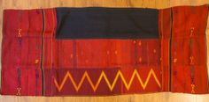 """Burmese Kachin Jinghpaw Skirt - A beautiful wrap-around skirt, or """"pukhang"""" from one of the Jinghpaw tribes in Kachin state, northern Burma. This piece is woven in three panels on a very narrow backstrap loom and then hand-sewn together. It is a lovely bright red colour and scattered with supplementary weft designs in different colours."""