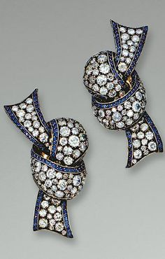 SAPPHIRE AND DIAMOND EAR CLIPS, MICHELE DELLA VALLE Each designed as a knotted ribbon, set with circular-cut diamonds and sapphires, mounted in silver and yellow gold,