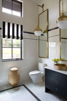 Stylish black and white bathroom boasting gold accents features Hicks Pendants hung in front of Restoration Hardware Pendant Leaner Mirrors mounted to a white upper wall finished with white subway backsplash tiles lined with black pencil tiles.