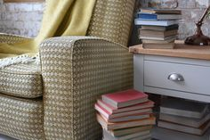 Earthy tones, books, grey furniture, vintage seat, coloured books, lamp table