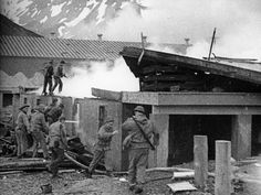 """U.S. soldiers fight a fire after an air raid by Japanese dive bombers on their base in Dutch Harbor, Alaska, in June 1942."""