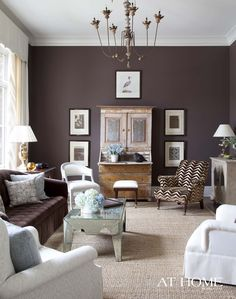 Benjamin Moore's Wood Grain Brown paint sets a rich, alluring tone for the family's formal living room. Accent pieces such as the mirrored coffee table, antique French chandelier