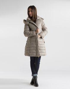 Plumífero largo de mujer acolchado beige, capucha desmontable y pieza extraíble de pelo de conejo, cinturón y cierre con cremallera y broches.