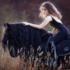 Freesian Horse with long black mane in a field of tall brown grass. Beautiful woman dressed in black with shiny black boots riding him. Romantic pretty horse photography.