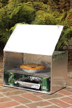 If you want to cook a meal while camping, here's a camp oven made out of a cardboard box and common household materials.