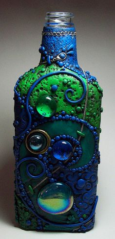 This is soooo cool!!! Polymer clay (with chain metal and glass cabochons) baked over a liquor bottle.