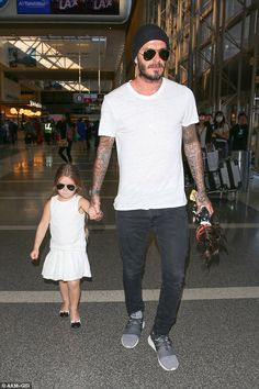 Daddy's girl: David Beckham ferried the couple's youngest child Harper - and only daughter - through the busy terminal and carried her doll too