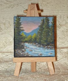 This painting is approximately 2 3/4 x 2 3/4 inches. It is painted with acrylic paint. The sides are painted a dark blue color. It comes with an easel. This painting is signed by the artist on the bottom edge of the canvas.