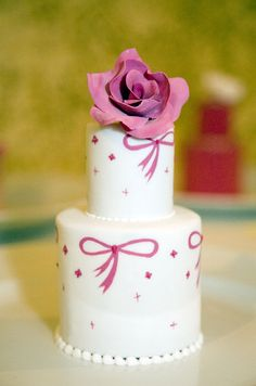 The pink fondant and gold stripes of this individual cake are topped with gold beads and a white sugar flower.