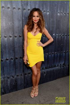 Chrissy Teigen in a Three Floor dress, Casadei shoes, a Kotur clutch, and jewelry by Carla Amorim and Melinda Maria.