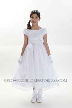 A classic style that will never go out of style! Dress features a short sleeve satin bodice and a double layer organza skirt. We love the subtle v style back of the dress. Comes with a removable sash and pin on flower. Zipper closure. The dress is fully lined for complete coverage to ensure that your princess stays comfortable. This dress is made from a designer label that upholds to the highest in quality and super cute style and value. Do not miss out on this dress! Proudly made in the…