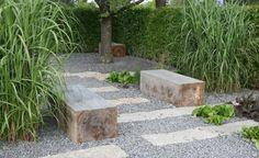 Formensprache konsequent umgesetzt: Rechteckige Natursteinplatten und quaderförmige Holzbänke beleben die graue Schotterfläche zwischen Hecken und hohen Gräsern