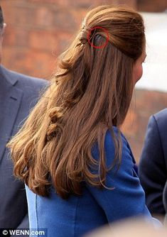 Slip: The Duchess' chic up-do inadvertently showed off a glimpse of grey on either side of her ponytail