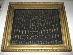 Key collection in gold-framed shadow box. Looks like all brass keys....
