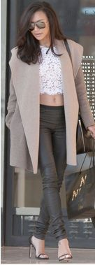 Naya Rivera wearing a lace crop top, leather pants, and an oversize coat