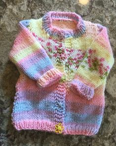 Knitted pastel banded cardigan with flower bursts http://www..com/lillians-blog/knitted-cardigan-with-baby-blossom-chunky-yarn #toddler sweater #chunky toddler cardigan #knitted toddler sweater