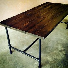 Industrial style reclaimed timber dining table with galvanised pipe base.