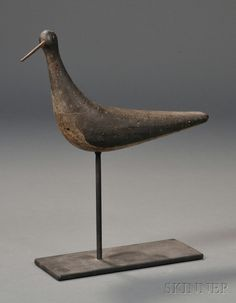 Carved and Painted Boomerang-shaped Snipe Shorebird Decoy, New England, early 20th century, the figure with wrought iron nail bill, mounted on a metal stand, (the body pierced by shot), overall ht. 12, lg. 9 in.