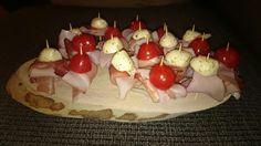 Tapas plankje. Gemarineerde Mozzarella em cherrytomaatjes met schinken.