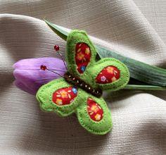 Jaro přichází Šitá brož z plsti světle zelené a hnědé barvy a bavlněné vzorované látky ve tvaru motýlka, zdobená korálky, s tykadly z krouceného drátku a červených korálků. Stříbrný brožový můstek, velikost 5 cm.  Květina na fotografii není součástí objednávky.