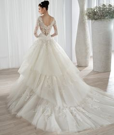 This romantic ball gown features an off the shoulder beaded lace neckline with long lace sleeves. The low scoop back is embellished with button closures and a tiered tulle Chapel train.