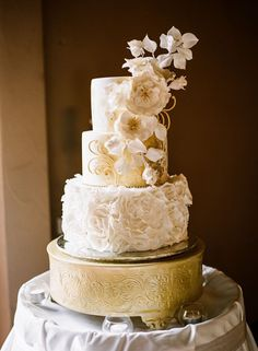 Gorgeous wedding cake with gold and white floral-themed details.