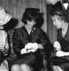 Jacqueline Kennedy admires the gold watch she received during the reception. Paris 1961
