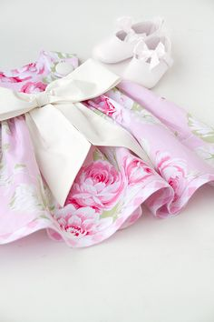 This gorgeous handmade baby dress is perfect for any special occasion. The pink rose colored cotton fabric is adorned with white polka dots, and a large white bow. This dress buttons at the shoulders
