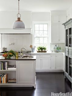 Contemporary white kitchen but with mahogany floors and antique fittings (lights, taps, windows)