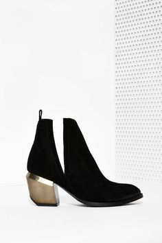 The Orwell Boot is made in black suede and features split shaft, slit at sides, bendable top, brushed metallic heel, and slightly pointed toe.