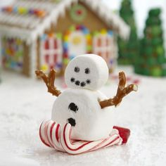 Sledding Marshmallow Snowman - What could be more whimsical than a marshmallow snowman speeding down the drifts on a candy-cane sled? Make one for your gingerbread house display!
