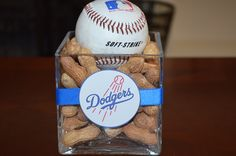 Small square vase containing peanuts and a baseball, wrapped with ribbon and a Dodger image.