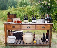 The couples favorite wines are displayed on a wooden side board with a towering arrangement of greenery.