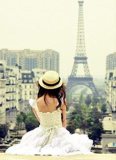 The cute girl in her dress looking at the Eiffel Tower. +