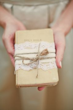 """""""Rings tied to a Bible with lace""""  - love it, but obviously, I'd use a different book."""