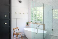 Modern Farmhouse Style Bathroom Design with Custom Black Linen Cabinets, Textured Walls, Double Stacked Herringbone Tile, Seamless Glass Shower, Seamless Glass Shower Door, White Tub, Brass Robe Hooks. Modern Farmhouse Bathroom, Modern Farmhouse Style, Linen Cabinets, Herringbone Tile, Glass Shower Doors, Black Linen, Washroom, Textured Walls, Hooks
