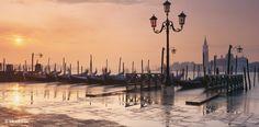 Wie verzaubert erscheint Venedigs Promenade in San Marco und die Insel San Giorgio Maggiore im rosafarbenen Licht der Abendsonne. Am Marktplatz überflutet Hochwasser das Kanalufer, das von Pfählen und vertäuten Gondeln markiert wird – Diese Karte hier online kaufen: http://bkurl.de/pkshop-211184 Art.-Nr.: 211184 Verzaubert | Foto: © David Noton Photography | Text: Rolf Bökemeier