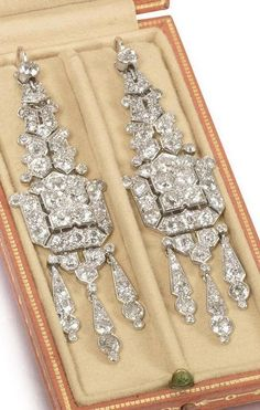 Cartier - A pair of Art Deco diamond pendent earrings, circa 1925. Each elongated plaque, composed of articulated geometric motifs, pierced and set throughout with old brilliant and single-cut diamonds, terminating in a similarly-set diamond tassel, each signed Cartier London, length 6.7cm. #Cartier #ArtDeco #earrings