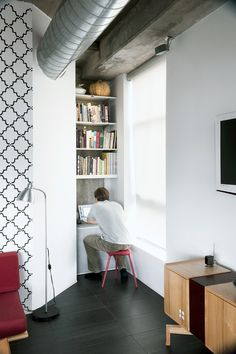 Arthur installed shelving from Ikea and poured a cast-in-place concrete shelf to create a small media nook. Photo by: Matthew Williams