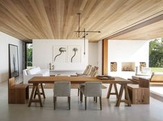 Because of the open floor plan, the living and dining areas flow directly onto the loggia when the glass doors separating the spaces are folded back. Inside and out, the ceiling is cedar and the floor is tinted concrete. Homeowner Klein collaborated with 1100 Architect on the interior decoration. The table was custom-designed by Lars Bolander in West Palm Beach.