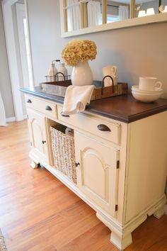 Farmhouse style dining room buffet/sideboard. Painted white, stained top. Bin pulls. Seagrass basket.