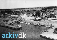 arkiv.dk | Fiskerihavnen Masnedsund. På billedet ses bl.a. stejlepladsen. Midt i billedet ligger den gamle Masnedsund station og til venstre ses bygning ved nuværende Kulturarkadens hovedindgang.  Fiskerihavnen blev opfyldt i forbindelse med opgørelse af cementsilo. 1955. Vordingborg Lokalhistoriske Arkiv, signatur B4169.