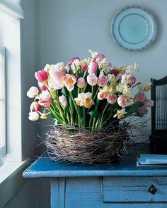 En korg med tulpaner och påskliljor som lindats med björkris blir härlig mitt på bordet. Påmarthastewart.comfinns fler instruktioner!