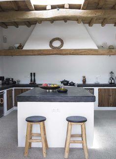 Bellissima cucina in muratura rustica, con isola centrale - abbinamento colori bianco, nero e legno - soffitto con travi in legno e pavimenti in cemento