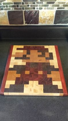 8Bit Mario End Grain Cutting Board 14x12.5x1 by SawdustAndMore, $160.00: I want to make one of these! This one uses hard maple, walnut, cherry, and paduak wood and is one inch thick. I imagine that each individual square is an inch. I would just need to figure out how to cut that many pieces that small and where in the world to get them from! I would also need a few more tools.