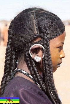Tuareg braids. Also an earring -- worn up and over the ear apparently.