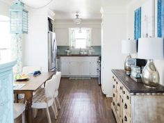 The butcher block countertops (which Kaylor installed herself) and light blue glass backsplash subtly contrast with the white cabinets and stainless steel.  Read more at Fisherman's Wife Furniture »  - GoodHousekeeping.com