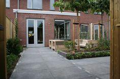 Tuin met grote tegels, dakbomen en verhoogde bloembakken