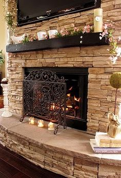 stacked stone fireplace, creme or beige walls, dark floors and white trim. classic.