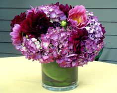 Purple hydrangea and dahlia modern centerpiece ... imagine this in blue. vase is wrapped with green leaf